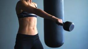 Een sportieve vrouw heft actief haar uitgestrekte hand met een gewicht op stock video