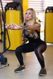Een sportvrouw die een oefening die van diepe hurkzit doen, in evenwicht brengen met handen, in de gymnastiek royalty-vrije stock afbeelding