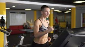 Een sportvrouw loopt intensief op een tredmolen, dient het gebruiken geschiktheidsclub in stock footage