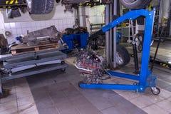 Een sportwagen die op een lift voor reparatie en onder het wordt opgeheven losgemaakt royalty-vrije stock afbeeldingen