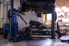 Een sportwagen die op een lift voor reparatie en onder het wordt opgeheven losgemaakt royalty-vrije stock foto