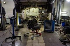 Een sportwagen die op een lift voor reparatie en onder het wordt opgeheven losgemaakt stock afbeelding