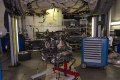 Een sportwagen die op een lift voor reparatie en onder het wordt opgeheven losgemaakt stock foto's