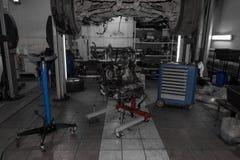Een sportwagen die op een lift voor reparatie en onder het wordt opgeheven losgemaakt stock foto