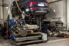 Een sportwagen die op een lift voor reparatie en onder het wordt opgeheven losgemaakt royalty-vrije stock fotografie