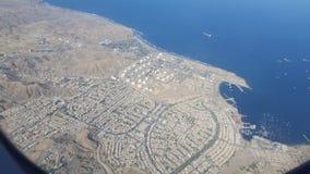 Een stad en een raffinaderij door het overzees met stralend stock afbeeldingen