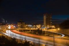 Een stad steekt en auto's die op de weg berijden aan Moderne gebouwen in nachtlichten royalty-vrije stock fotografie