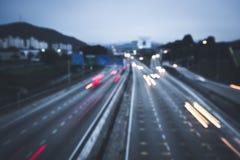 Een stadsverkeer dat bij nacht wordt gevangen die bokeh techniek gebruiken Stock Afbeeldingen