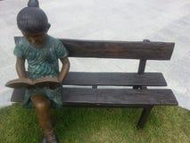 Een standbeeld van een meisje die een boek lezen terwijl het zitten op de houten bank royalty-vrije stock foto's