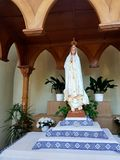 Een standbeeld van een vrouw in een lange kleding en een mantel die haar hoofd behandelen Een vrouw houdt de palm van haar handen Royalty-vrije Stock Afbeeldingen