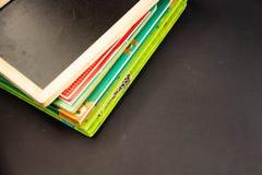 Een stapel boeken en een houten raad op een zwarte achtergrond royalty-vrije stock fotografie