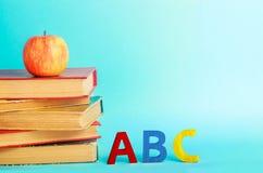 Een stapel boeken met een rode appel en de brieven van het Engelse alfabet van ABC bevinden zich op een blauwe achtergrond Het co stock afbeeldingen