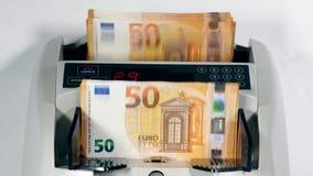 Een stapel euro bankbiljetten wordt mechanisch geteld stock footage