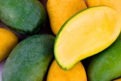 Een stapel gele rijpe mango en verse groene mango en halve mango op wit achtergrond gezond fruitvoedsel Royalty-vrije Stock Foto's