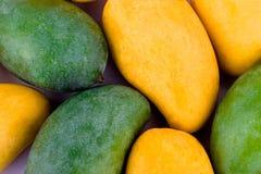 Een stapel gele rijpe mango en verse groene mango op wit achtergrond gezond geïsoleerd fruitvoedsel Stock Afbeeldingen