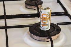 Een stapel honderd-dollar rekeningen op een gasfornuis in het centrum van gascomfort, het gas brandt niet stock foto