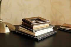 Een stapel houten kader, een lamp, een notitieboekje en potloden op het bureau stock afbeelding