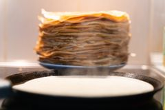Een stapel kant-en-klare gebraden pannekoeken de pannekoeken zijn gebraden op een zwarte pan stock afbeelding