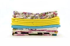 Een stapel kleurrijke kussenslopen over een witte achtergrond stock foto's