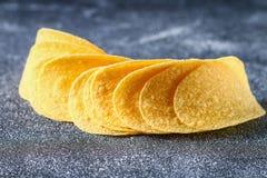 Een stapel knapperige spaanders op een grijze donkere lijst snack royalty-vrije stock afbeeldingen