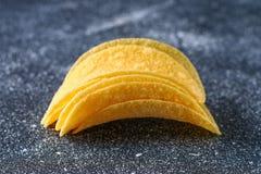 Een stapel knapperige spaanders op een grijze donkere lijst snack royalty-vrije stock fotografie