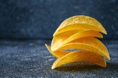 Een stapel knapperige spaanders op een grijze donkere lijst snack royalty-vrije stock foto