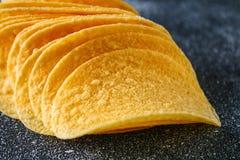 Een stapel knapperige spaanders op een grijze donkere lijst snack royalty-vrije stock afbeelding
