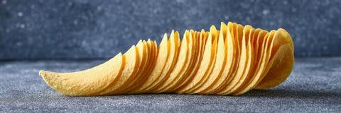 Een stapel knapperige spaanders op een grijze donkere lijst snack stock afbeeldingen