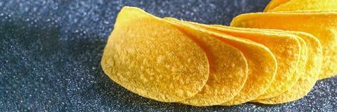 Een stapel knapperige spaanders op een grijze donkere lijst snack royalty-vrije stock foto's