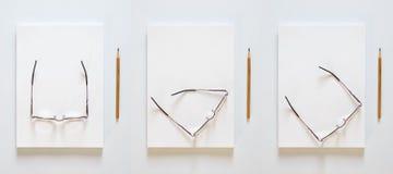 Een stapel lege bladen van document Potlood en glazen in verschillende posities inzake een witte achtergrond stock foto's