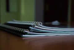 Een stapel notitieboekjes en handboeken voor het dagelijkse werk stock afbeeldingen