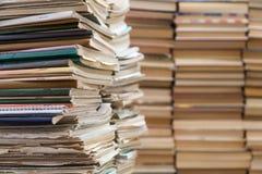 Een stapel oude schoolnotitieboekjes en een stapel handboeken of boeken royalty-vrije stock foto's