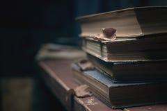 Een stapel oude uitstekende boeken op een rode houten lijst en droge bladeren royalty-vrije stock foto's