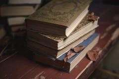 Een stapel oude uitstekende boeken op een rode houten lijst en droge bladeren royalty-vrije stock foto