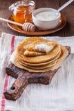 Een stapel pannekoeken met zure room en honing Stock Foto's