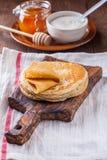 Een stapel pannekoeken met zure room en honing Stock Afbeeldingen