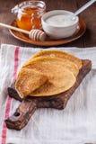 Een stapel pannekoeken met zure room en honing Stock Afbeelding