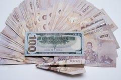 Een stapel Thais Baht en honderd dollars op een witte lijst met een vliegtuig stock afbeeldingen