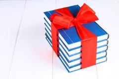 Een stapel van boeken bond met een rood lint op een witte houten lijst Een gift op de achtergrond van een bord royalty-vrije stock fotografie