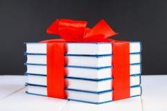 Een stapel van boeken bond met een rood lint op een witte houten lijst Een gift op de achtergrond van een bord stock foto