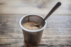 Een stapel van bruine suiker in staalkom met lepel Stock Foto
