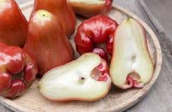 Een stapel van djamboevruchten met een plak in een houten dienblad op de lijst Stock Afbeelding