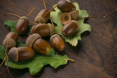 Een stapel van eikels van eiken en groene bladeren op een houten achtergrond royalty-vrije stock fotografie