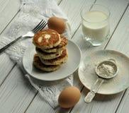 Een stapel van gebraden kaaspannekoeken, een vork op een wit linnenservet, een glas melk, secveral eieren en een plaat met bloem Stock Foto