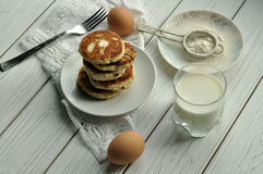 Een stapel van gebraden kaaspannekoeken, een vork op een wit linnenservet, een glas melk, secveral eieren en een plaat met bloem Stock Afbeeldingen