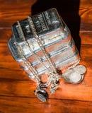 Een stapel van gegoten zilverstaven, diverse zilveren muntstukken en juwelen op een achtergrond van mahonie royalty-vrije stock foto's