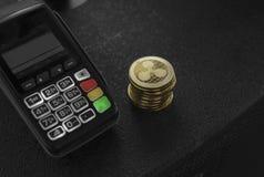 Een stapel van gouden Rimpelingscrypto muntmuntstukken en POS terminal Rimpelingen Cryptocurrency Elektronische handel, zaken, fi royalty-vrije stock afbeelding