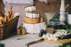 Een stapel van kaashoofden in een document, daarna een gesneden kaas, mand brood en druiven, wijn en installatiestoppen stock foto