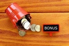 Een stapel van muntstukken met bord dat met Bonus op houten achtergrond wordt geschreven stock afbeelding