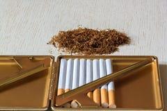 Een stapel van natuurlijke tabak op een witte houten lijst en sigaretten in een sigaretgeval smoking royalty-vrije stock afbeelding